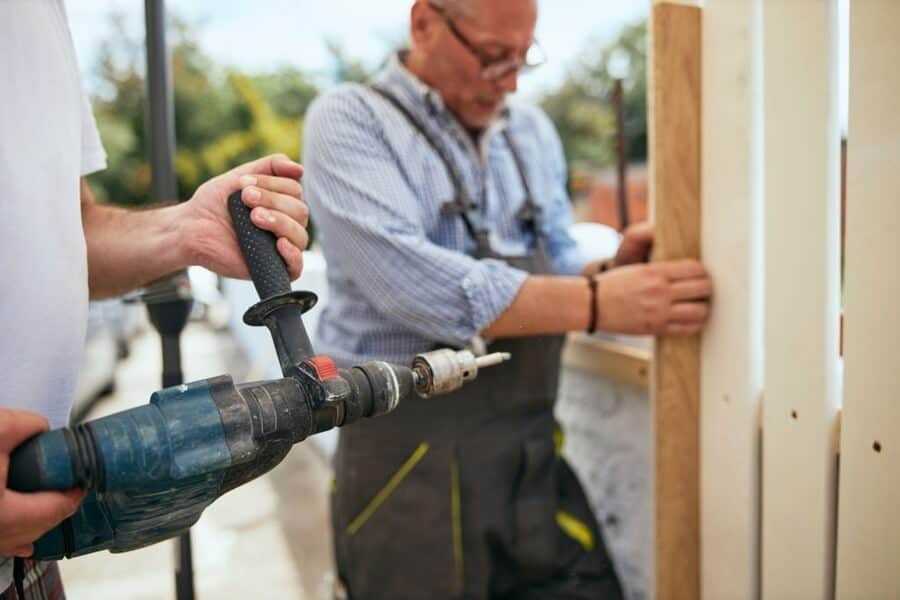 two professional worker building wooden fence