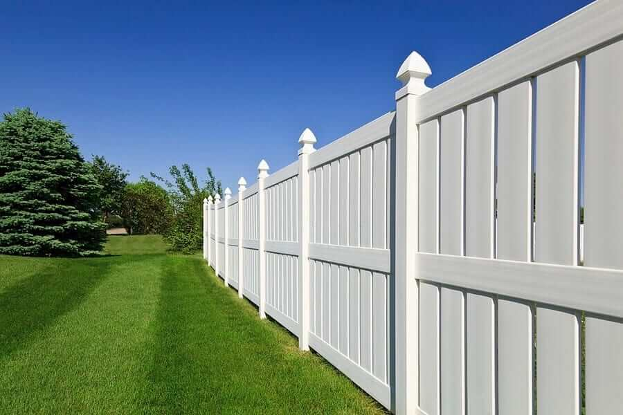 A simple white fence in backyard
