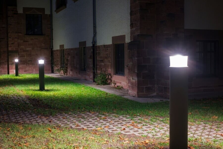 Outdoor lights (lanterns, bollards) in front of an old administration building illuminating a walkway in the garden at night